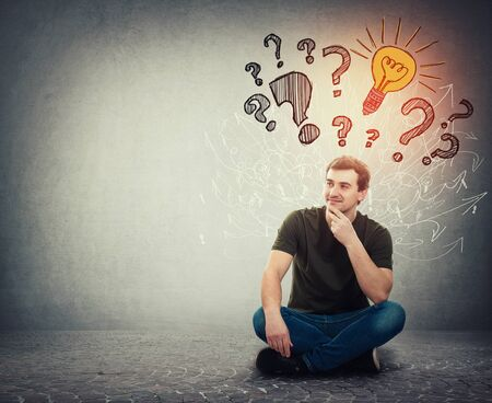 Photo for Pensive man sitting on the floor holding hand under chin has many questions as interrogation marks above head and one bright idea as lightbulb glowing through the arrow mess. Genius thinking concept. - Royalty Free Image