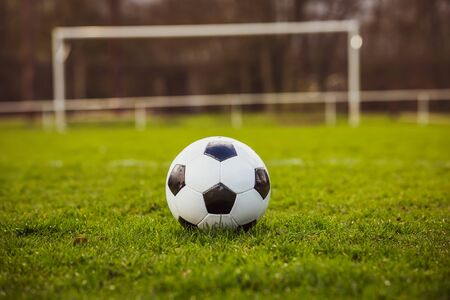 Photo pour Classic soccer ball typical black and white pattern, placed on stadium turf. Traditional football ball on the green grass lawn with copy space. - image libre de droit