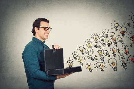 Businessman opens his briefcase filled with brilliant ideas as different lightbulbs comes out of the box. Ingenious boss shows the business portfolio, shares his creativity and genius with employees.