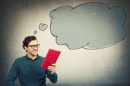 Photo for Happy young man, student guy, holding an interesting red book, reading the textbook title. Education concept, learning process. Guy choose what to read. Empty thought bubble comes out of his head. - Royalty Free Image