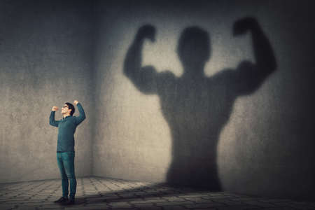 Photo pour Confident man flexing muscles imagine super power as casting a shadow of muscular bodybuilder showing biceps. Strong person facing his fears. Personal development, inner strength, motivation concept. - image libre de droit