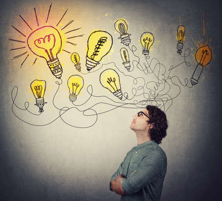 Photo for Creative businessman, thinking of great ideas, looking at bright lightbulbs on the wall. Business worker search for solutions to solve the problems, genius planning concept. Smart and ingenious guy. - Royalty Free Image