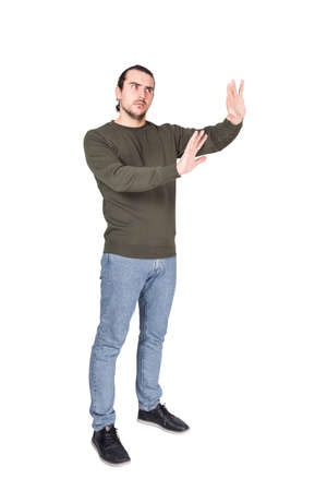 Photo pour Full length of cautious man showing stop gesture with his palms, arms outstretched as deny or refuse, gesturing prohibition, no sign, isolated on white background. Rejection or refusal concept. - image libre de droit