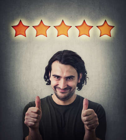 Photo pour Contented young man, shows both thumbs up gesture, slick smiling to camera. Attractive casual guy, happy emotion, gives like, approval symbol and five stars rating, positive feedback - image libre de droit