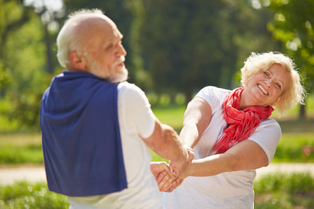 Old man and senior woman dancing together in a garden in summer