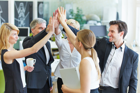 Happy business team making high five with their hands in the office