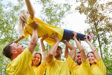 Photo pour Team raises a woman together at a team building workshop - image libre de droit