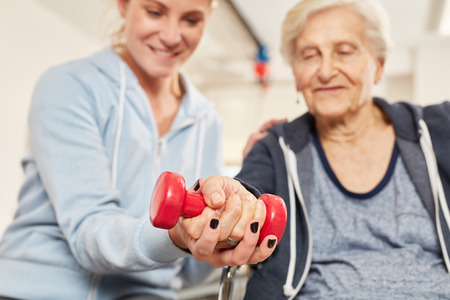 Photo pour Physiotherapist helps elderly woman with healthy dumbbell training in rehab - image libre de droit