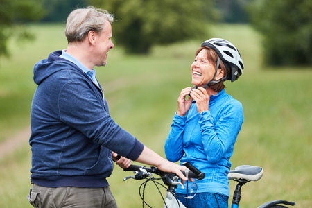 Photo pour Active senior woman puts on a bicycle helmet with partner before the bike ride - image libre de droit