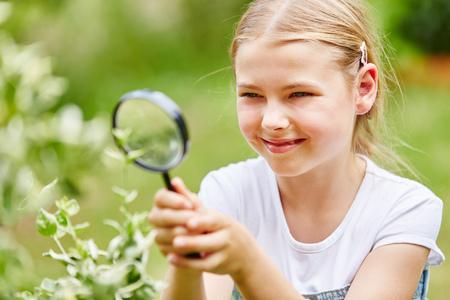 Foto de Girl researches with magnifying glass in garden and explores nature with curiosity - Imagen libre de derechos