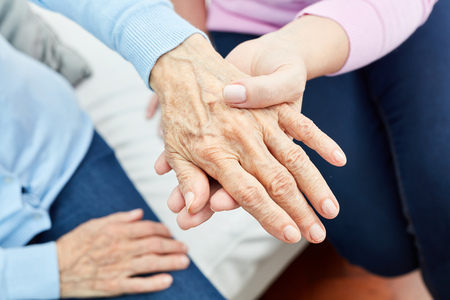 Photo for Female nursing assistant or nurse consolingly holds the hand of an old woman - Royalty Free Image