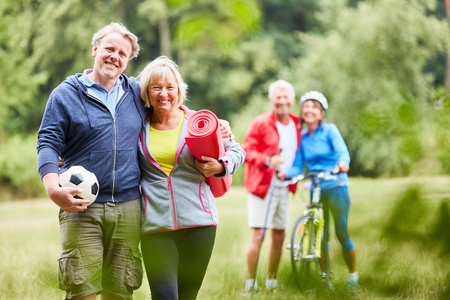 Photo for Vital senior couple and sporty friends together in the summer in the park - Royalty Free Image