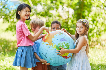 Photo pour Multicultural group of children in nature is holding a world globe - image libre de droit