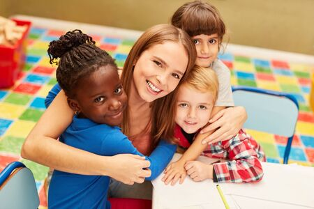 Photo pour Happy woman as a teacher or childminder together with children in the day care center - image libre de droit