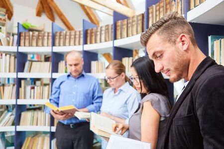 Photo for Group of people while reading book together in the library of community college - Royalty Free Image