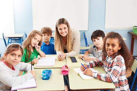 Foto de Group of multicultural elementary students in tutoring lessons with teacher - Imagen libre de derechos