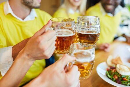 Photo pour Hands hold beer glass while toasting in a bar or restaurant - image libre de droit