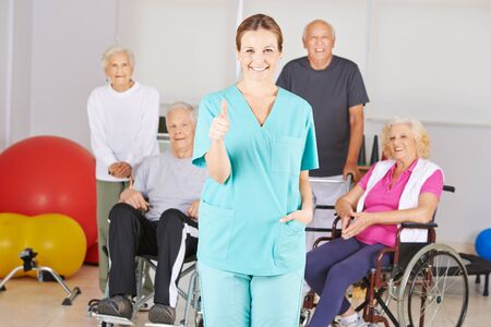 Photo for Nurse in nursing home holds thumbs up with a group of seniors - Royalty Free Image