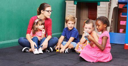 Foto de Children in kindergarten look at a picture book with the educator - Imagen libre de derechos