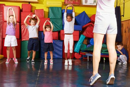 Photo pour Happy group of kids together while kid sports in preschool - image libre de droit