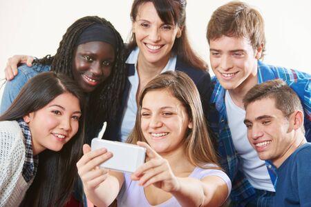 Foto de Laughing group of students takes a selfie with teacher together - Imagen libre de derechos