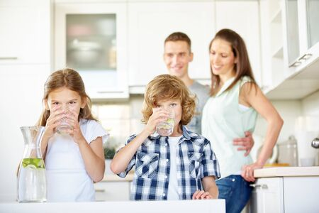 Photo for Children drink fresh water with limes in the kitchen in front of their parents - Royalty Free Image