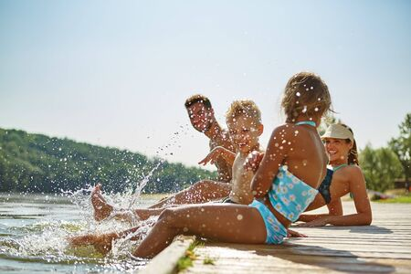 Photo for Happy family by the lake in summer holding feet in water - Royalty Free Image