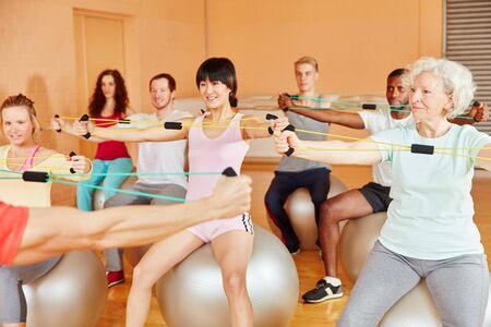 Photo pour Group with a senior woman stretches during class in the fitness center - image libre de droit