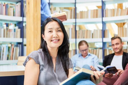 Photo pour Asian woman as a student reading a book in the reading room in the university library - image libre de droit