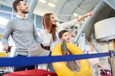 Photo pour Happy family in the airport terminal is happy about the punctual departure on vacation - image libre de droit