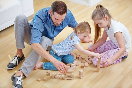 Foto de Family with father and two children plays together with building blocks at home - Imagen libre de derechos