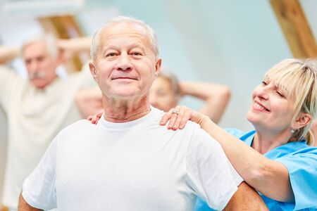Photo for Therapist supports senior man in healthy back training - Royalty Free Image
