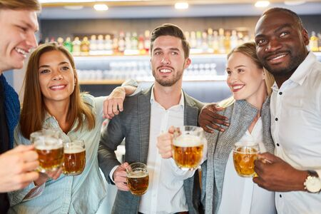 Photo for Group of friends having beer together in pub or bar after work - Royalty Free Image