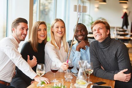 Photo pour Young people as friends in the restaurant take self portrait with the selfie stick - image libre de droit