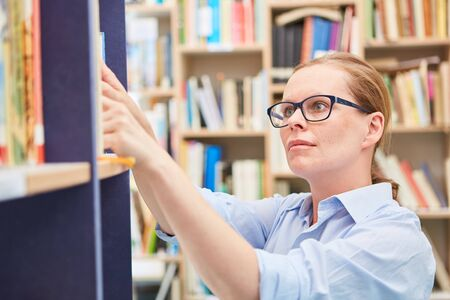 Photo for Woman as a librarian looks for book on shelf of a library of the community college or the university - Royalty Free Image