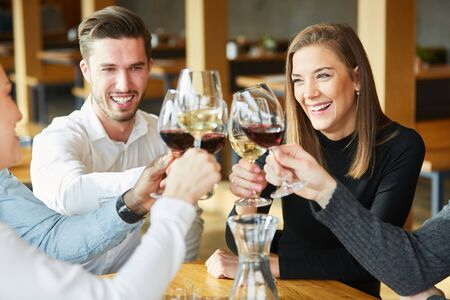 Photo for Young people toast with glass of wine in the restaurant and celebrate together - Royalty Free Image