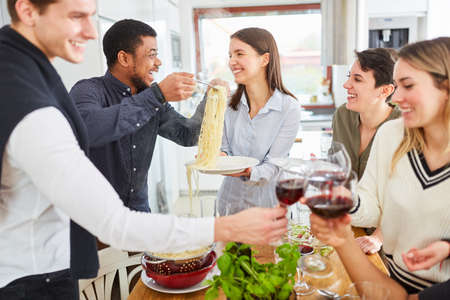 Photo pour Lunch together in student flat share with pasta and red wine - image libre de droit