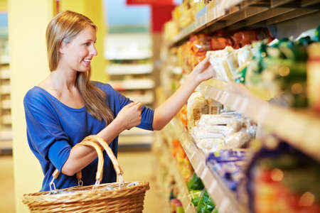 Photo pour Woman stands in supermarket with shopping basket on shelf for pasta - image libre de droit