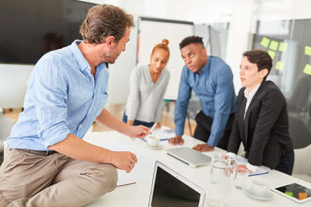 Photo for Consultant for coaching or consulting a young start-up team in a workshop - Royalty Free Image