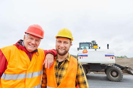 Foto de Construction workers as colleagues as a team on the construction site of road construction with excavators - Imagen libre de derechos