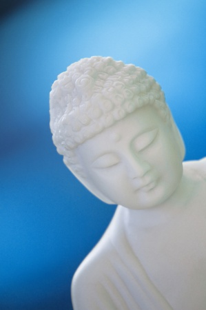 white buddha sculpture on bue background