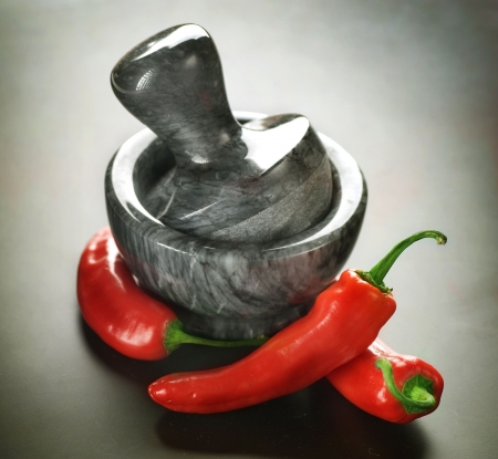 Mortar with pestle and Herbs.Over black background