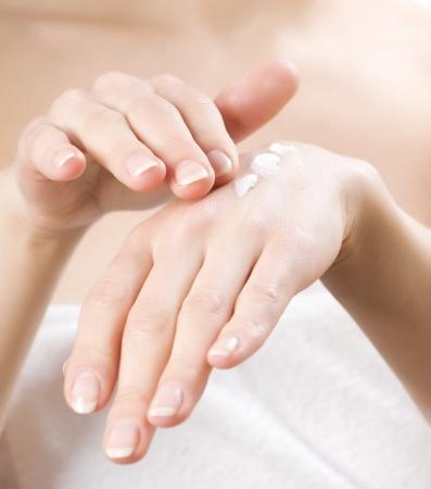 Photo pour Female applying moisturizer to her Hands after bath.Skincare concept - image libre de droit