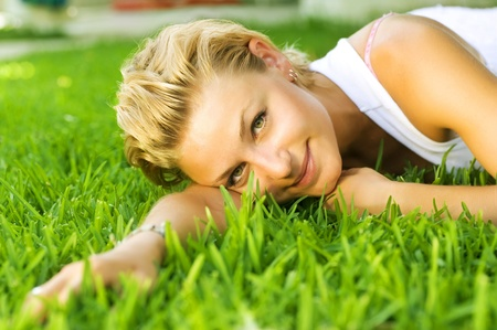 Beautiful healthy Young Woman relaxing on the green grass