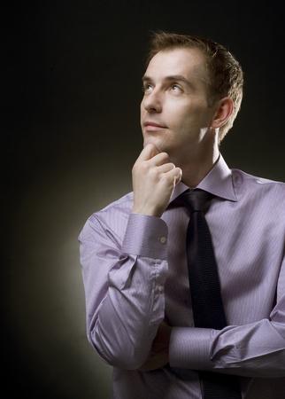 Handsome Businessman thinking. Black background