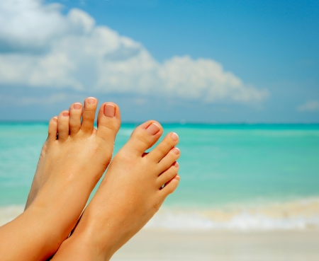Vacation Concept  Woman s Bare Feet over Sea background