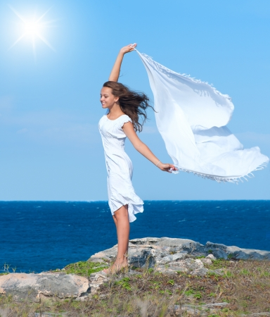 Freedom Concept  Girl with White Scarf standing on the Rock