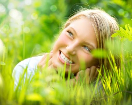 Beautiful Smiling Girl in Green Grass