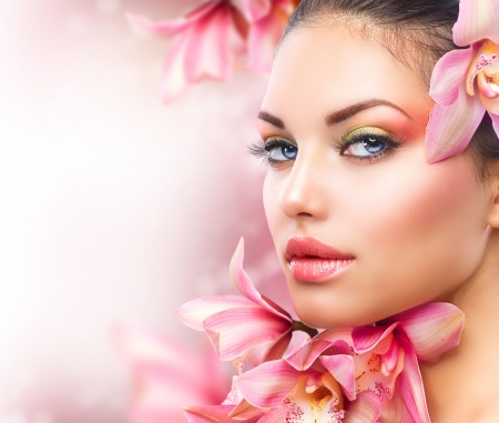 Foto de Beautiful Girl With Orchid Flowers  Beauty Woman Face - Imagen libre de derechos