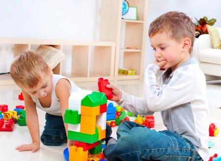 Foto de Children Boys playing with construction set on the floor  - Imagen libre de derechos